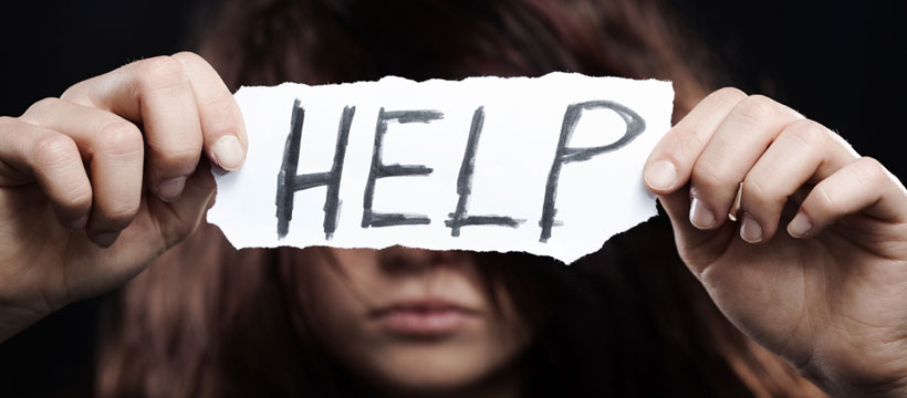 woman holding help sign