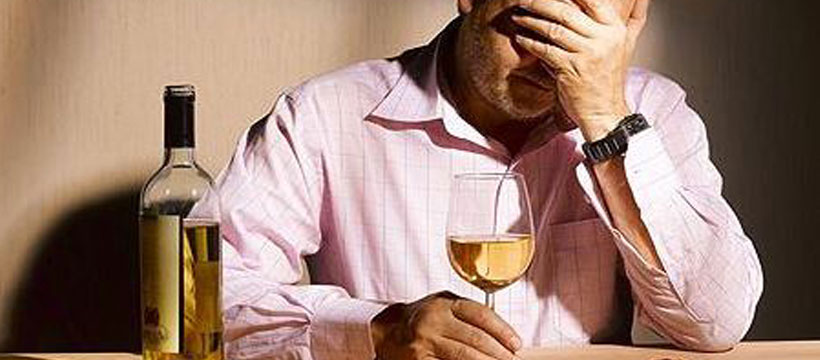 depressed man with glass of wine